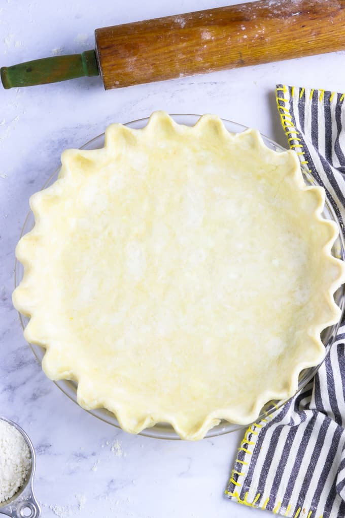 Unbaked pie crust in a pie pan with rolling pin on the side.