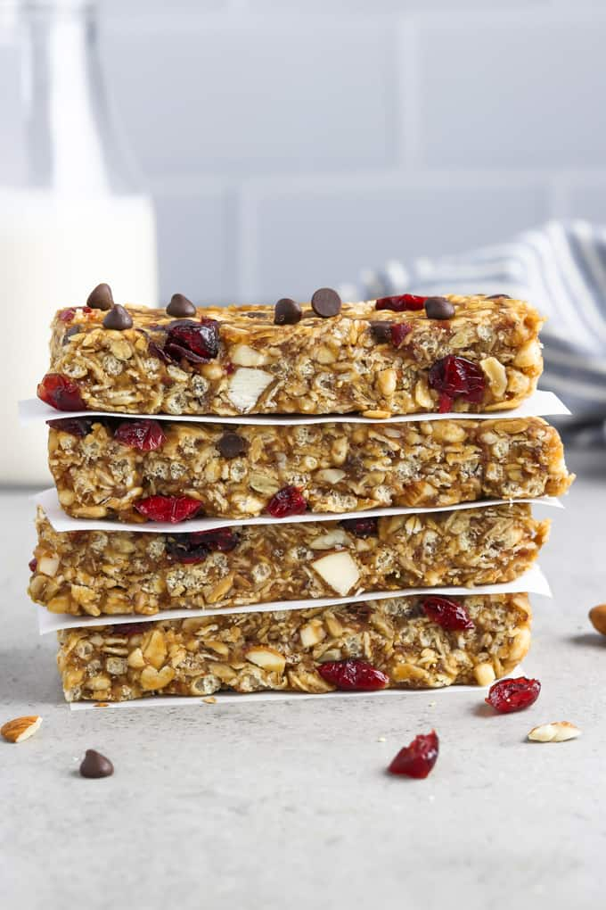 4 vegan granola bars stacked on top of each other. Striped napkin and bottled milk in the background.