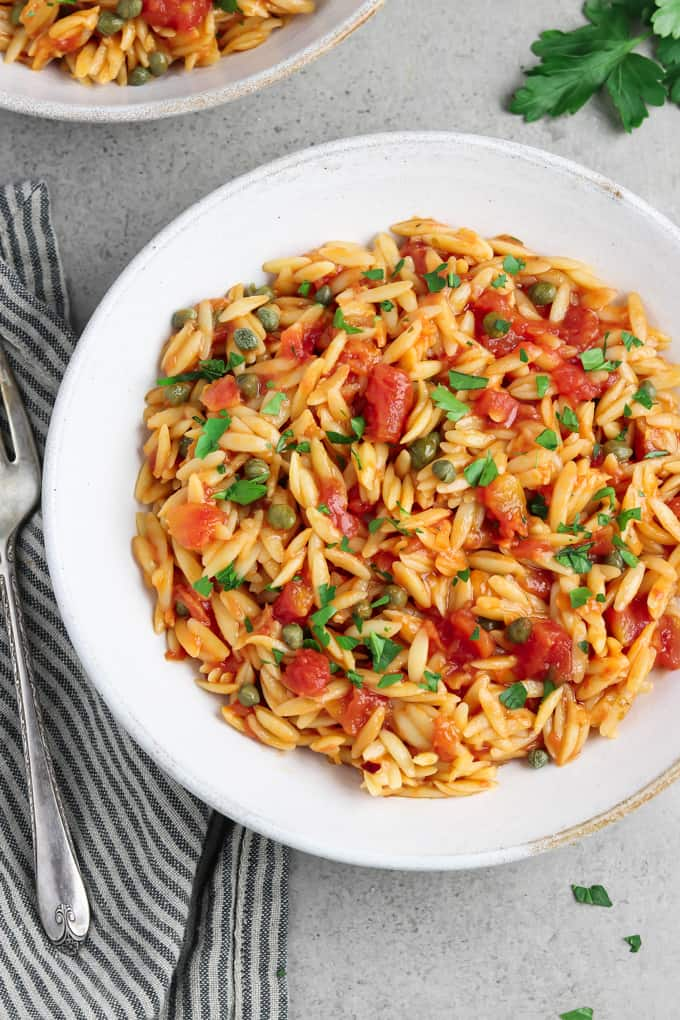 Overhead view of fully cooked tomato orzo in q white bowl.