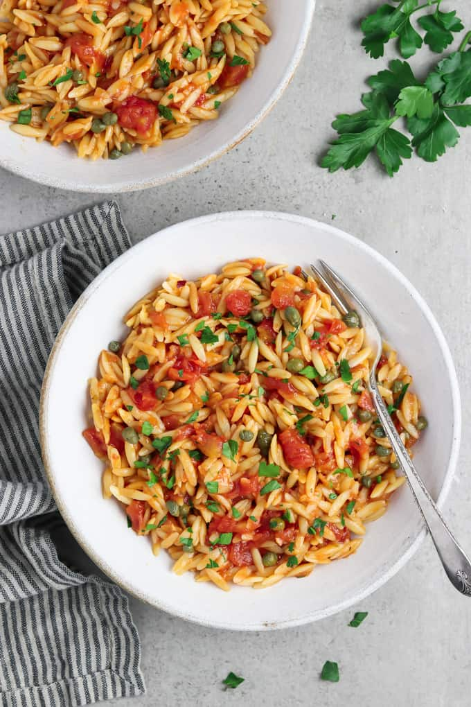 two bowls of tomato orzo with a fork in one bowl. Fresh parsley on the side.
