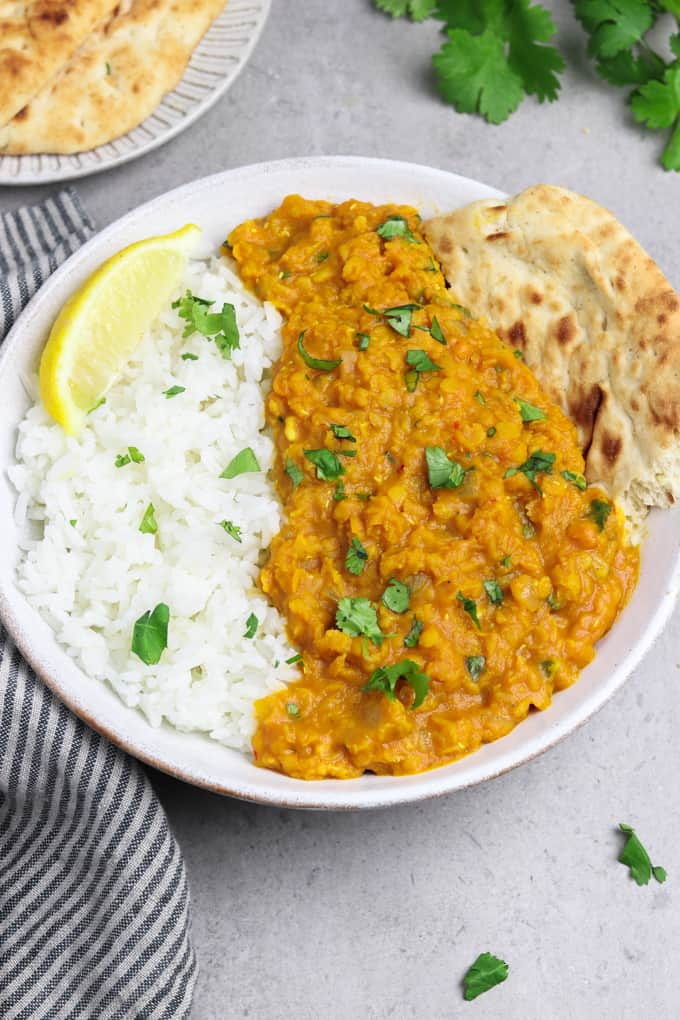 Red lentil dahl in a white bowl alongside rice. Topped with lemon, cilantro and naan.