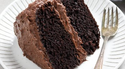 vegan chocolate cake on a white plate with a fork on the side.