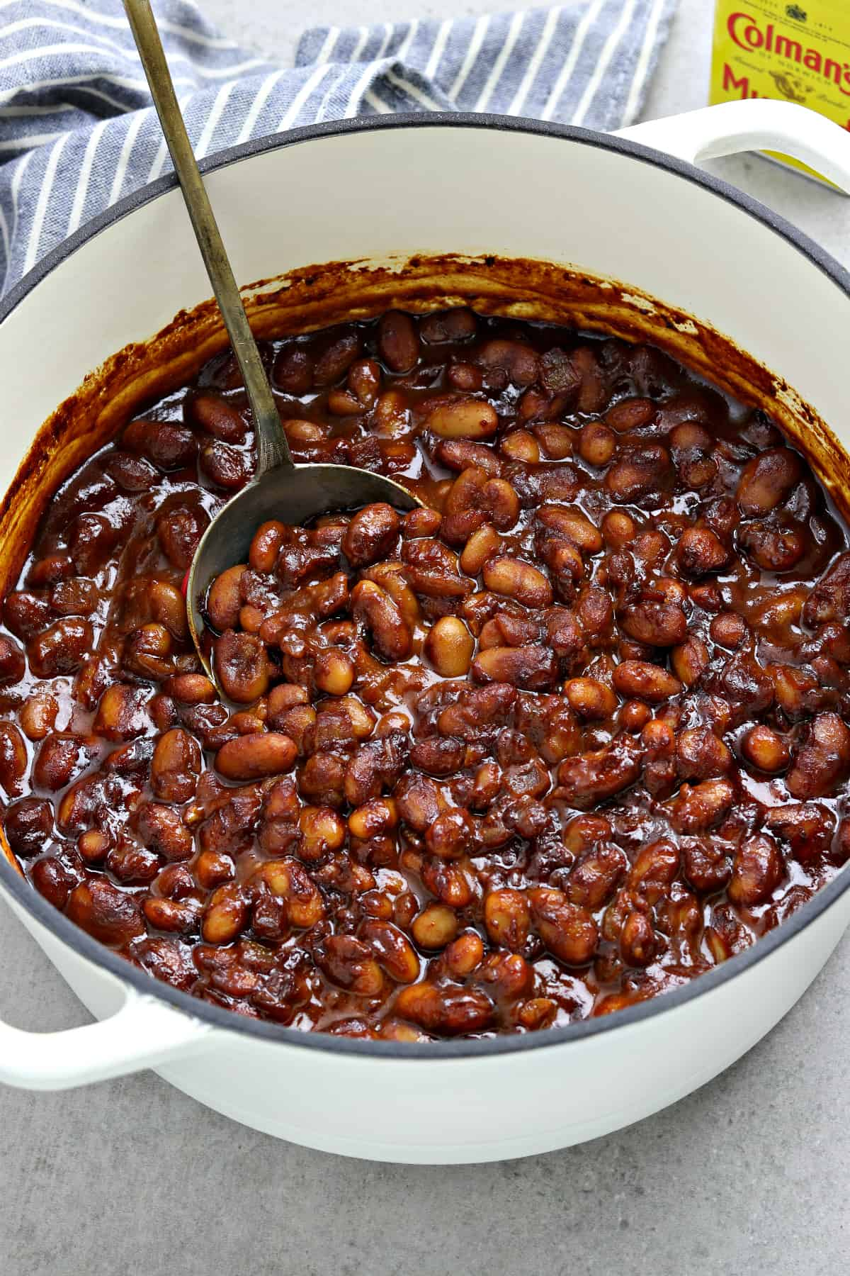 Fully cooked beans in a white pot with a spoon in the middle Napkin and mustard powder in the background.
