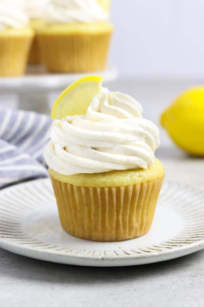 one frosted cupcake on a white plate. Lemon cupcakes on a stand in the background.