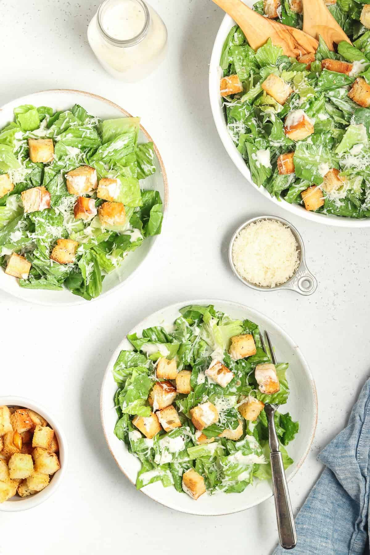 Full overhead view of 3 bowls filled with vegan caesar salad. Croutons, blue napkin and parmesan on the side.