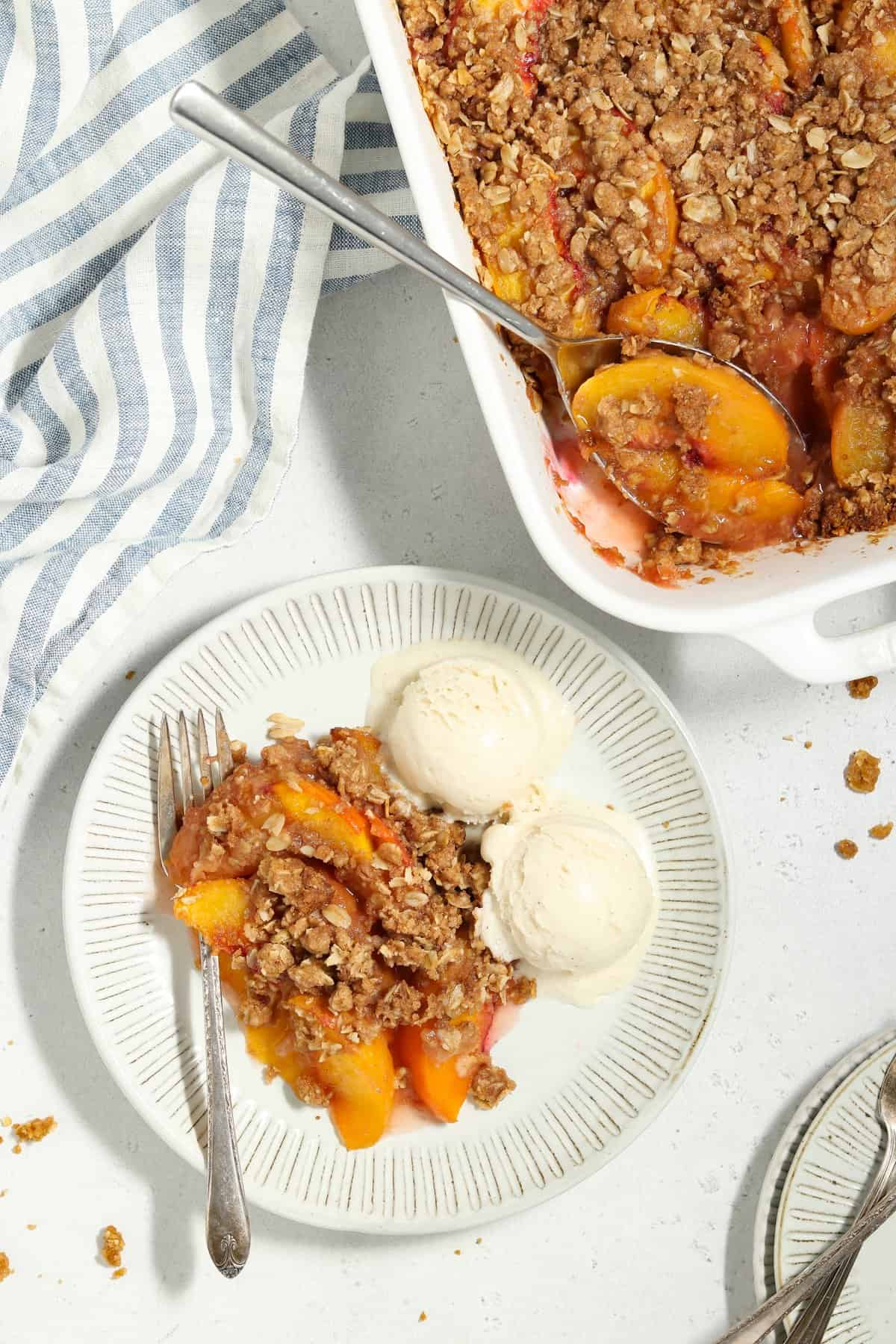 Overhead view of peach crisp and ice cream on a plate. Casserole dish on the side.