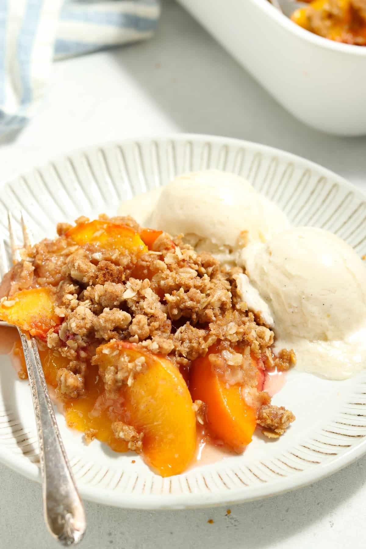 Close up view of peaches and ice cream on a white plate.