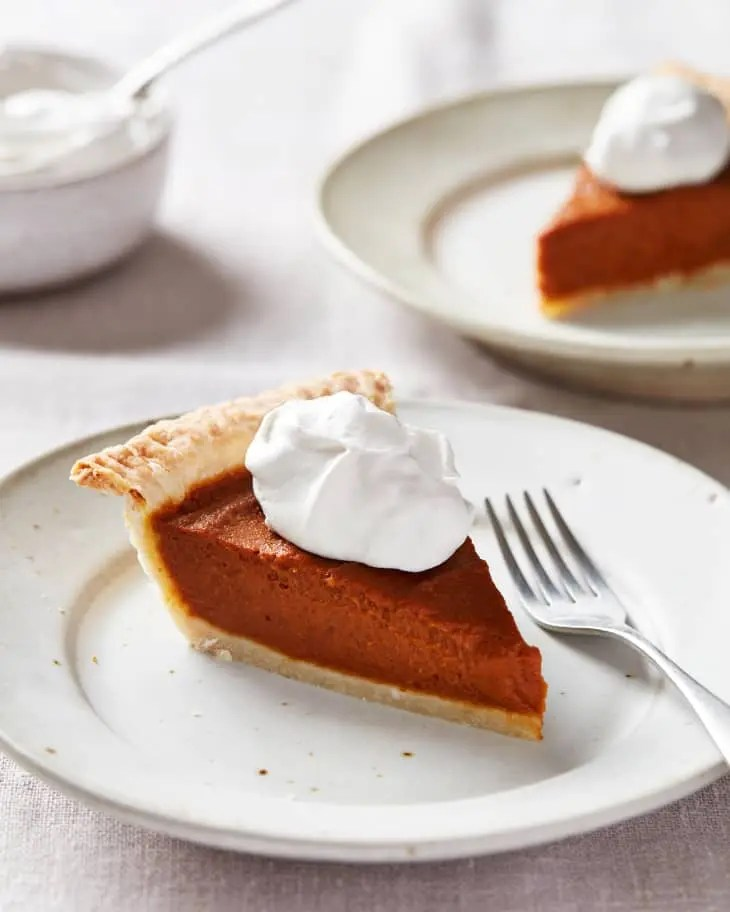 Slice of vegan thanksgiving pumpkin pie on a plate, another on the back