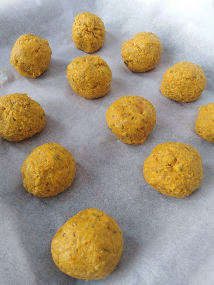 baking tray with parchment paper full of carrot bread balls