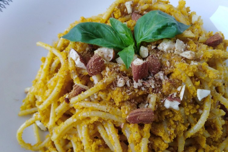 close-up of plate with spaghetti with carrot pesto sauce and almonds on top