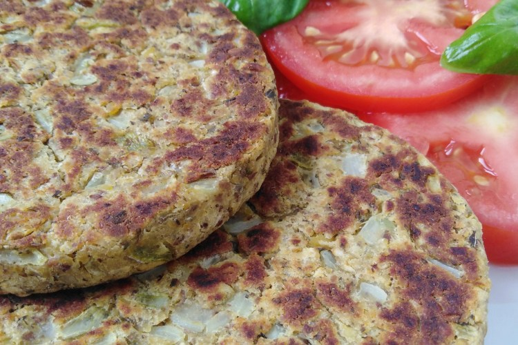 vegan chickpea burgers on a plate with tomatoes and basil salad