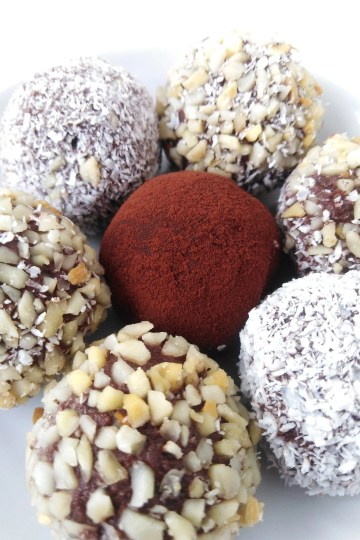 close-up of plate with vegan chocolate banana truffles covered in nuts and coconut