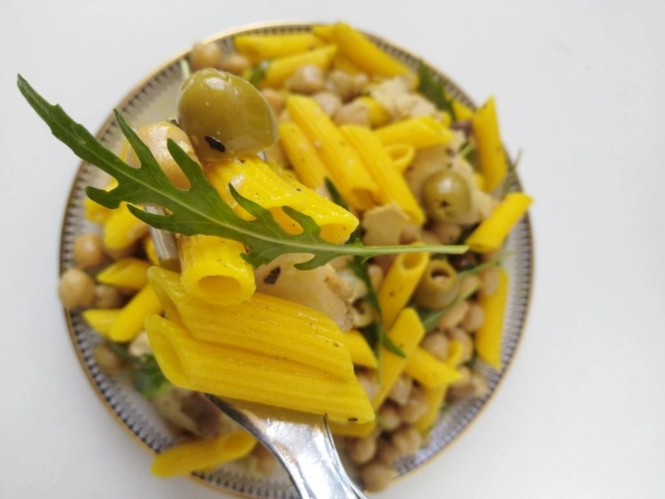 picture from above of fork holding pasta and chickpeas salad with plate on the background