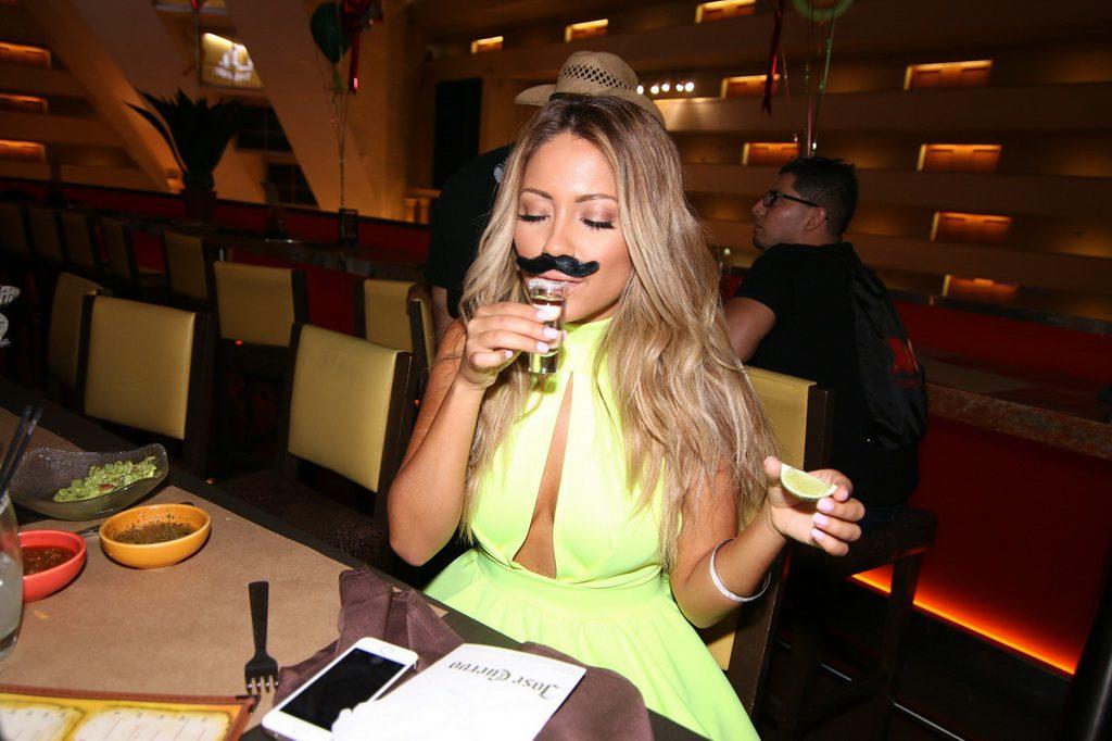 Jessica Burciaga taking a shot of Don Julio tequila with Cinco de Mayo mustache