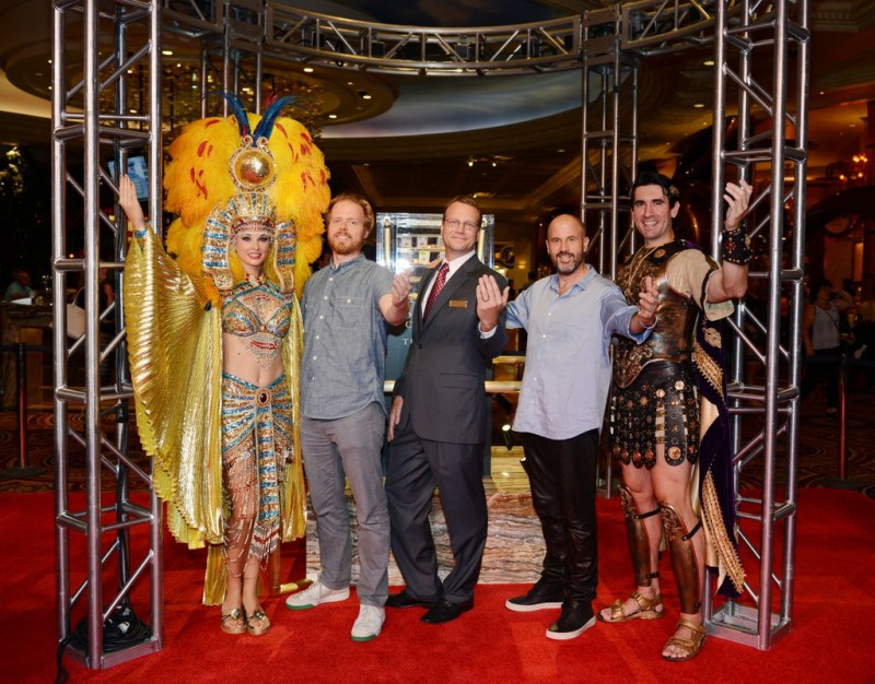 From left to right: co-author Nils Johnson-Shelton, Caesars Palace Vice President of Marketing Eric Proffitt and co-author James Frey pose with Caesar and Cleopatra in front of the gold display.