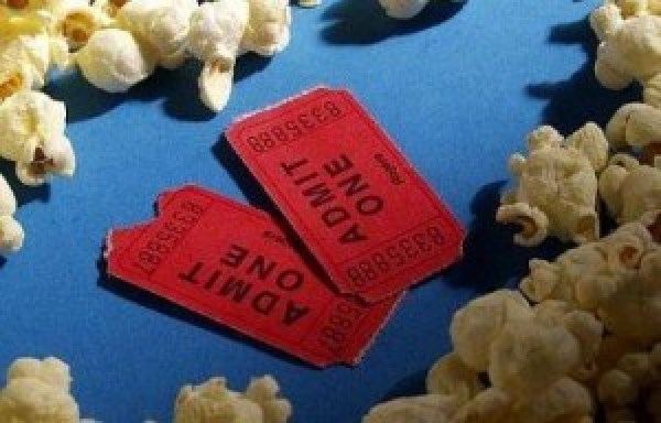 Two movie tickets surrounded by popcorn