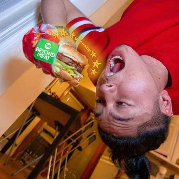 Man upside down taking bite of Beyond Meat burger from Carl's Jr.