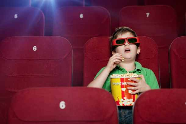 Boy in movie theater with 3D glasses on eating a bucket of popcorn