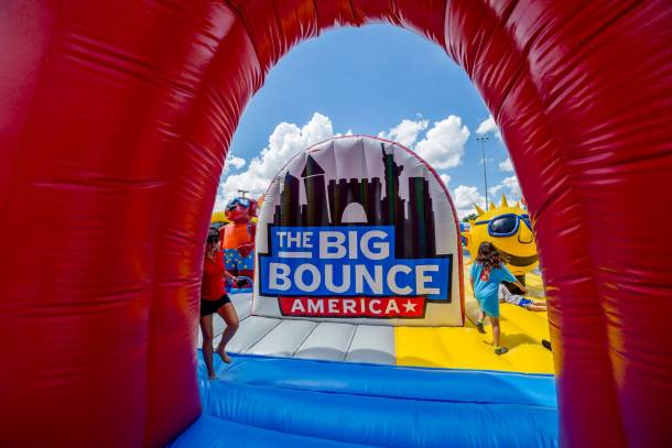 The Big Bounce America logo hanging in the bounce house with kids jumping