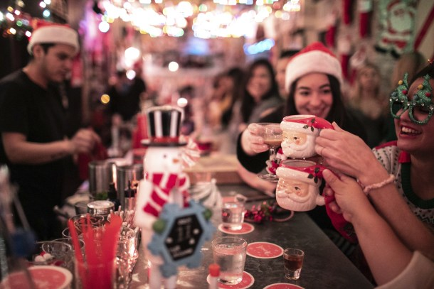 Festive Holiday bar with girls drinking from santa mugs