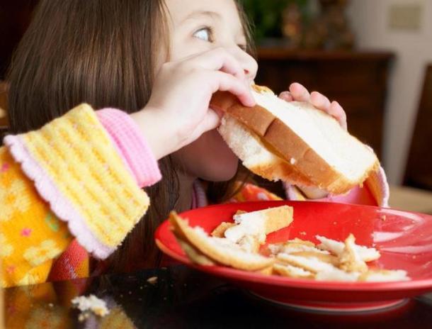 student food distribution, girl eating sandwich on plate