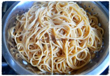 Cooked spaghetti transferred to colander to drain