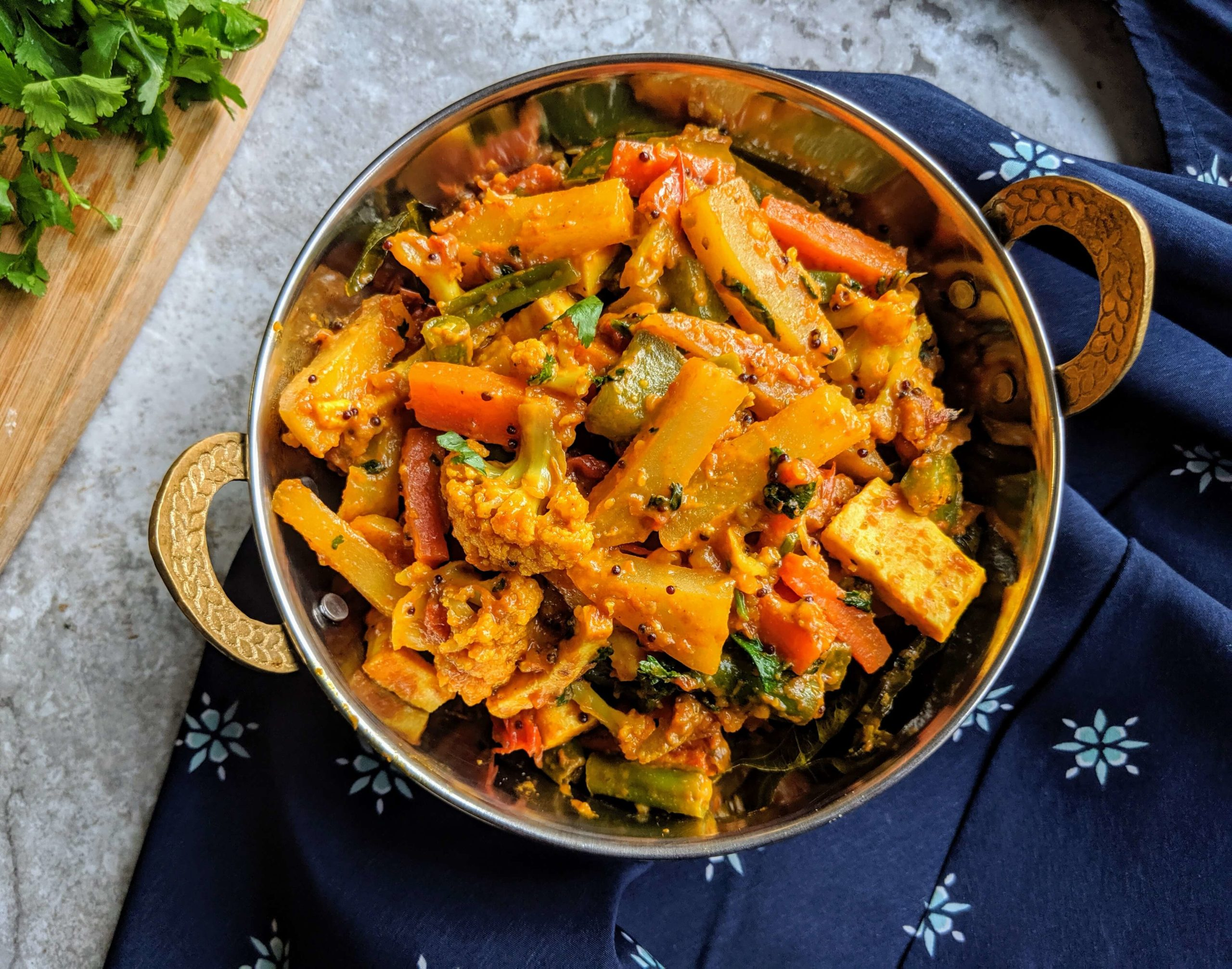 Vegetable Jalfrezi is a semi-dry curry made with a tangy colorful blend of stir fried mixed vegetables cooked in a thick spicy tomato base.