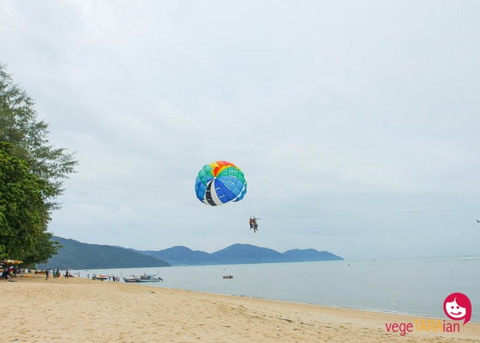 A paraglider takes off from Batu Ferringhi beach, Malaysia