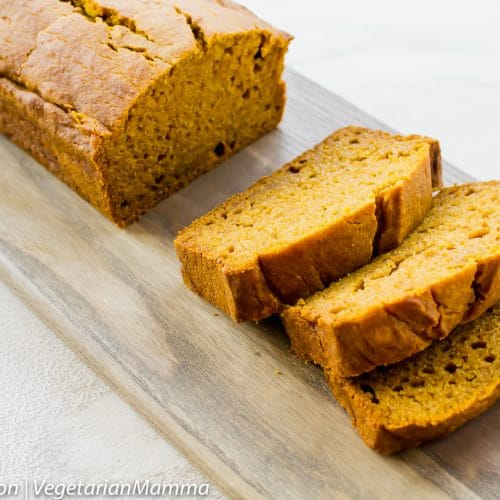 Pumpkin bread on wooden board atop white table