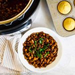 Overhead shot of vegan baked beans made in the instant pot with some corn bread muffins.