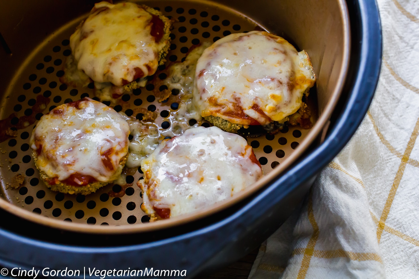 Air Fryer Gluten Free Eggplant Parmesan topped with cheese in the air fryer basket.