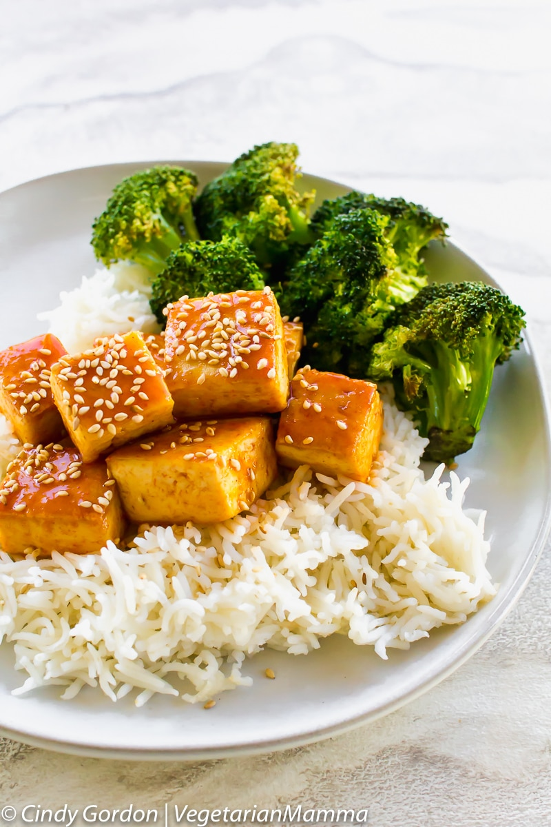 a plate of rice topped with saucy tofu and broccoli, topped with sesame seeds