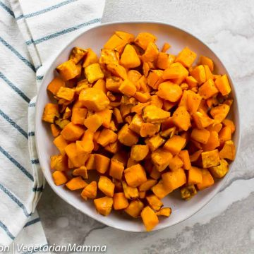 Sweet potato cubes in round bowl with white and black striped cloth on white and gray table