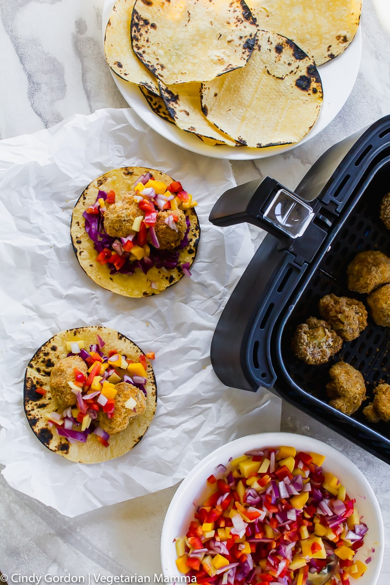 Overhead shot of cauliflower pieces cooked in air fryer basket and contructed tacos with mango slaw on top.