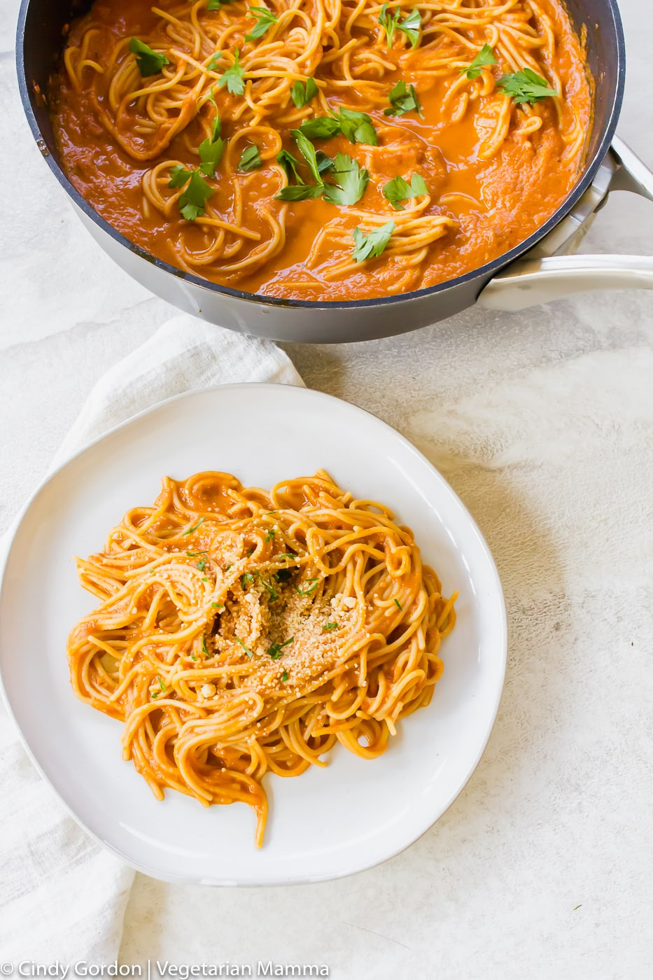 Vegetarian Spaghetti Sauce served on a white plate aside the skillet full of pasta and sauce