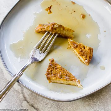 Almost eaten french toast on a plate with a fork stuck into a piece