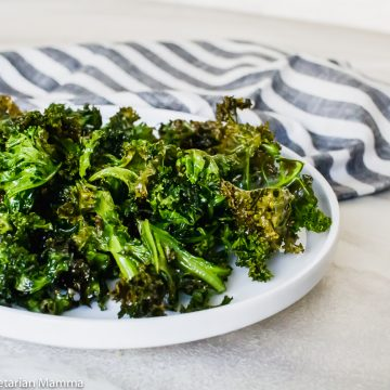 Side view of air fryer kale chips in round white bowl