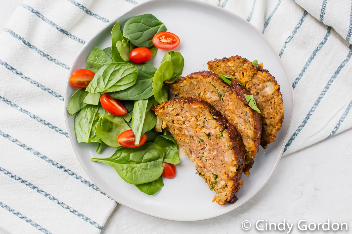 Vegetables and meatloaf on a round white plate with a white cloth with blue stripes