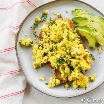 tofu scramble over toast with avocado slices on a white plate
