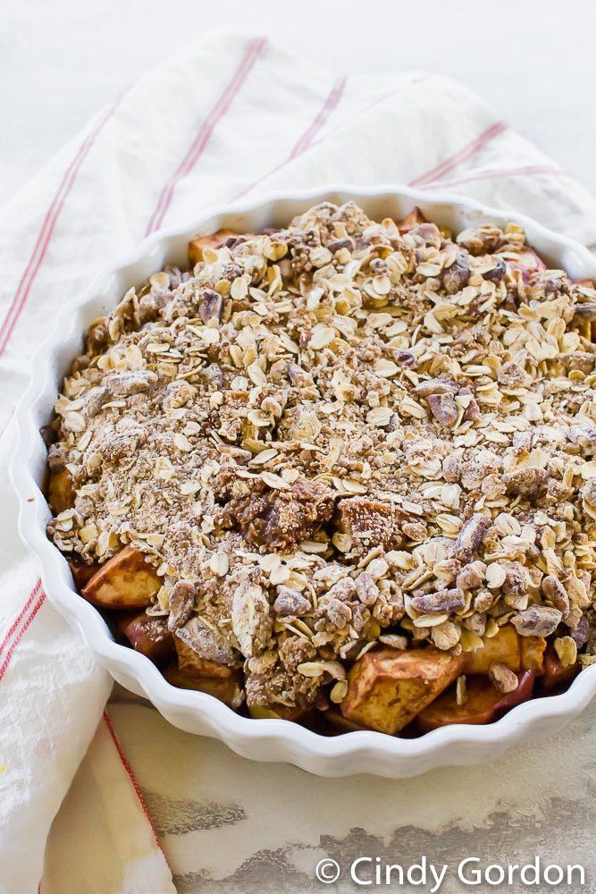 a pie pan of vegan apple crisp with a red striped kitchen towel