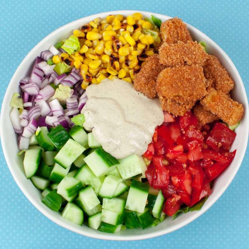 Salad with cucumber, vegan chicken, tomato, lettuce, corn, red onion, and vegan caesar dressing.