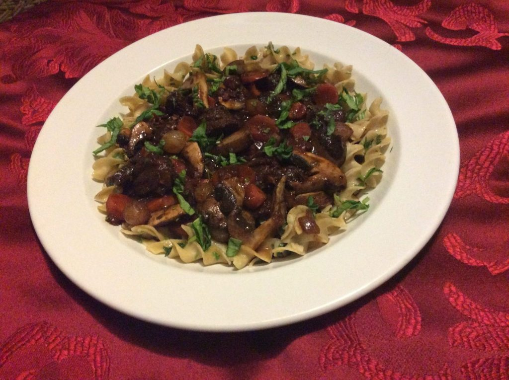 Beef chunks in tomato teriyaki sauce with baby tomatoes, mushrooms, spinach on whole wheat noodles