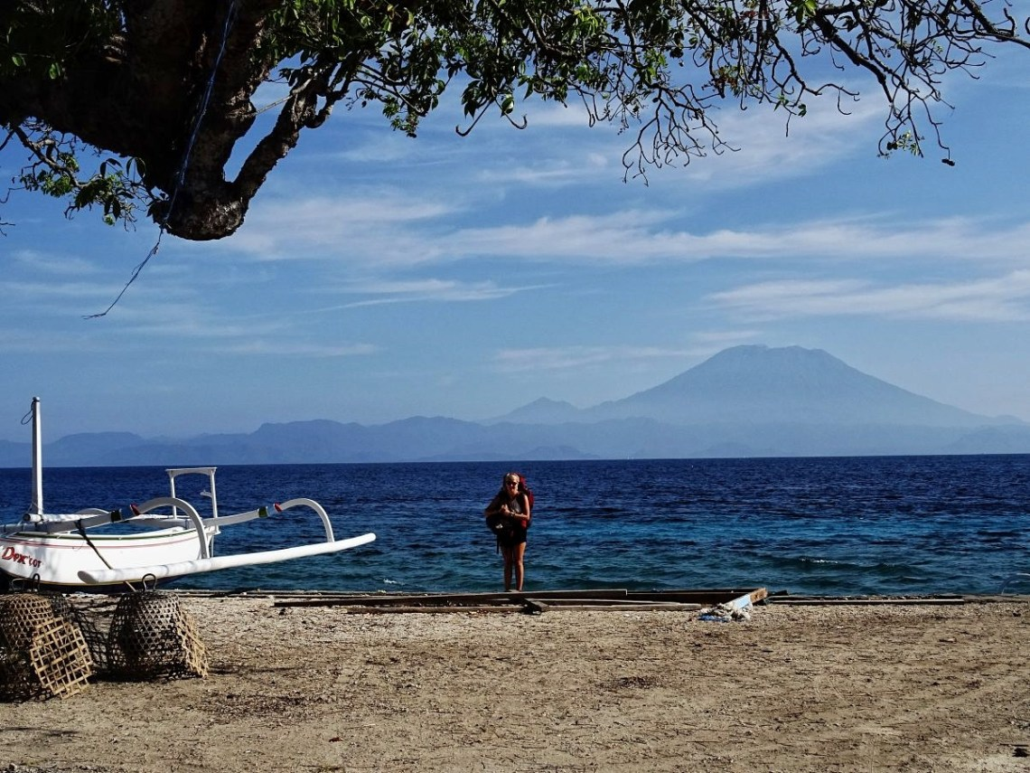 Backpacker on beach with volcano behind her