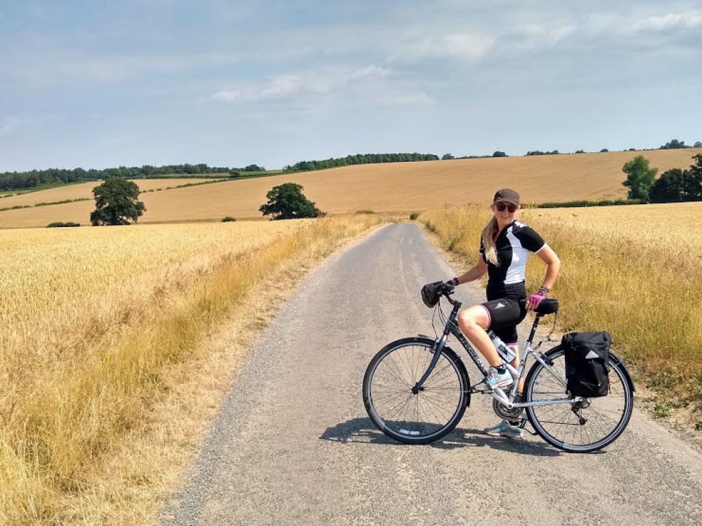 Girl cycling on bike in farmers field