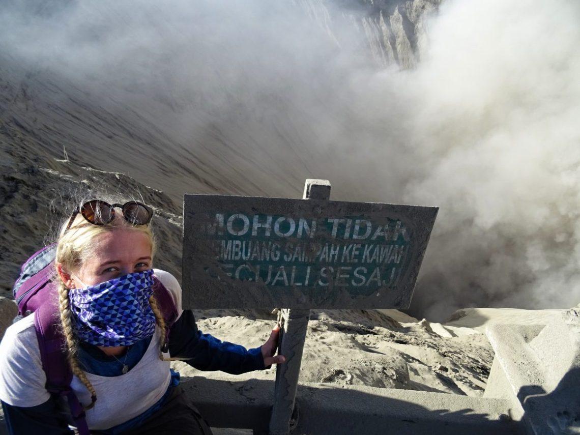 Girl sitting on edge of volcano