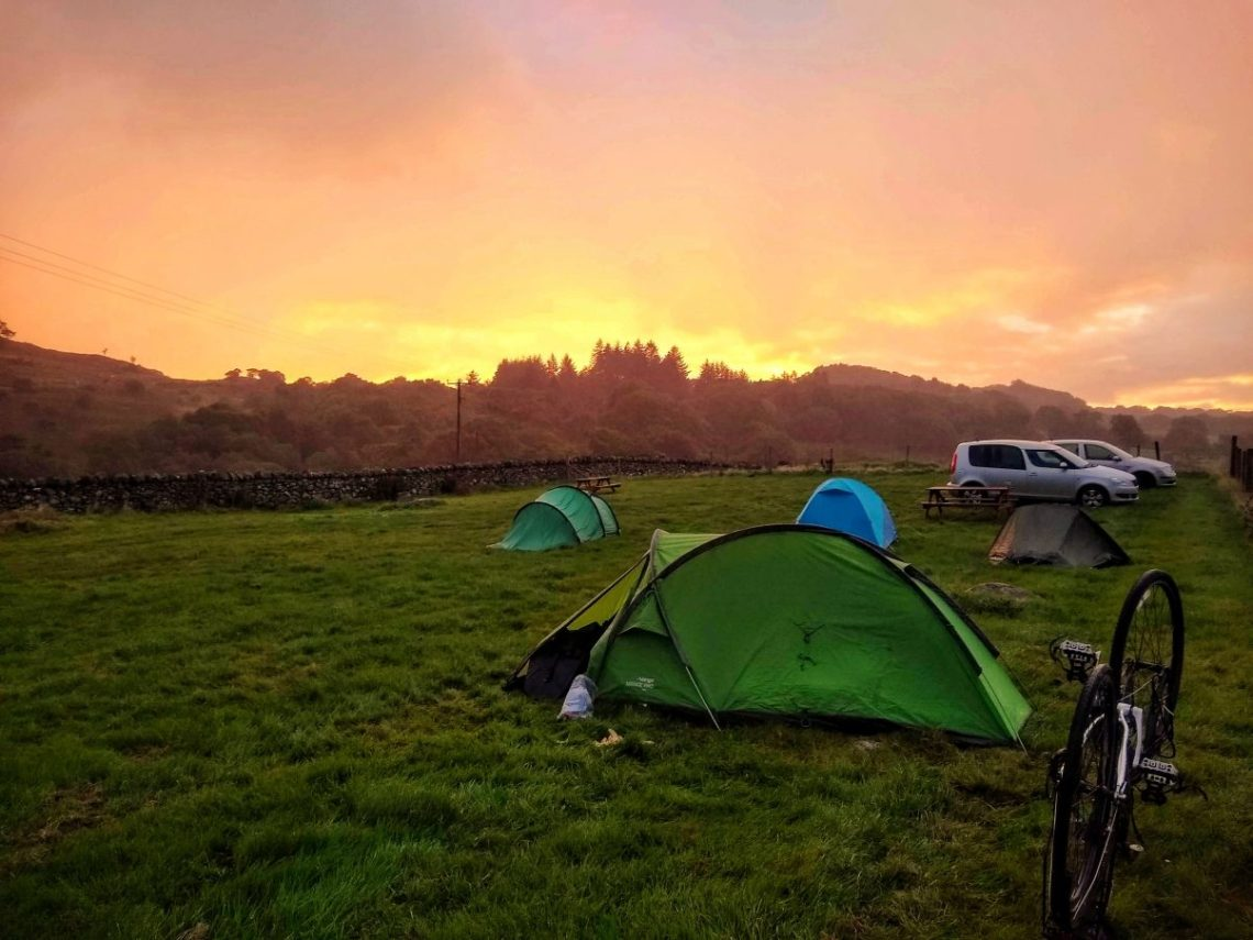 Sunrise over a tent in mountains