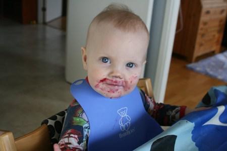 Cirka ettårigt barn ler mot kameran med kladdig mun