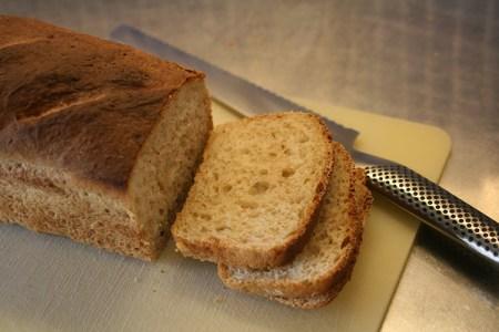 Ett bröd på skälbräda, två skivor har skurits, kniven ligger ovanför