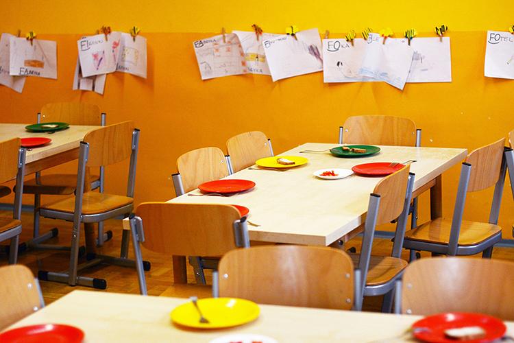 Bord med stolar i en sal, dukat med färgglada tallrikar