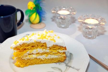 Tårtbit i tre gula lager med vit fyllning. Vitt och gunst strössel ovanpå, tända ljus och en pysselkyckling i bakgrunden.